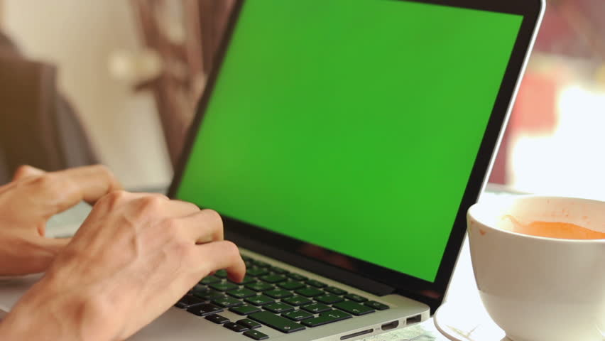 Close-up of male hands using laptop with green screen at cafe, man's hands typing on laptop keyboard in interior, side view of freelancer using computer in cafe | Shutterstock HD Video #24134821