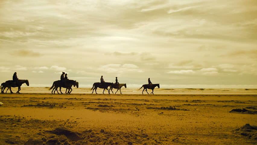 People enjoy horseback riding on sandy beach in Long Beach, Washington, real time, sepia filter.