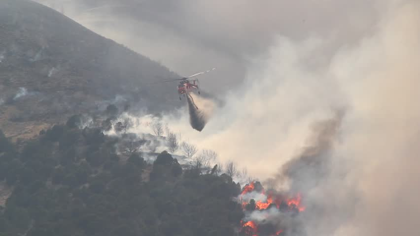 A helicopter battles a gigantic wildfire on a dry mountainside, dropping hundreds of gallons of water on the flames.