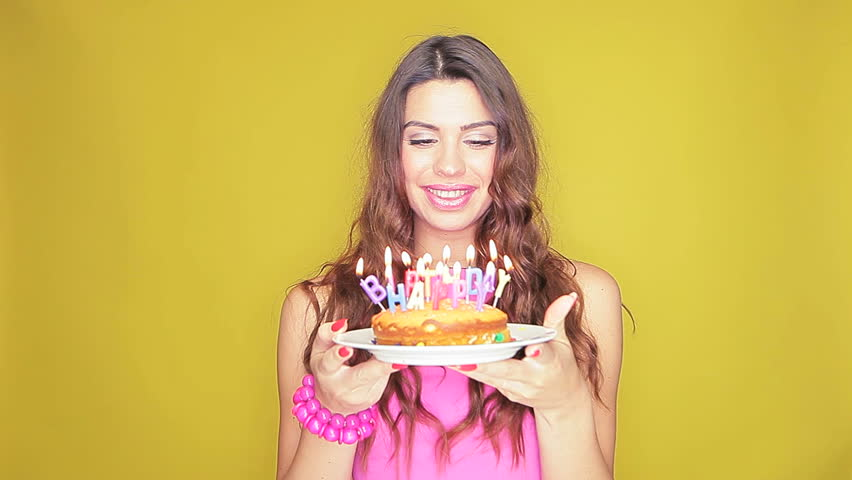 Beautiful smiling birthday girl holding her cake in both hands as she looks at all the burning candles