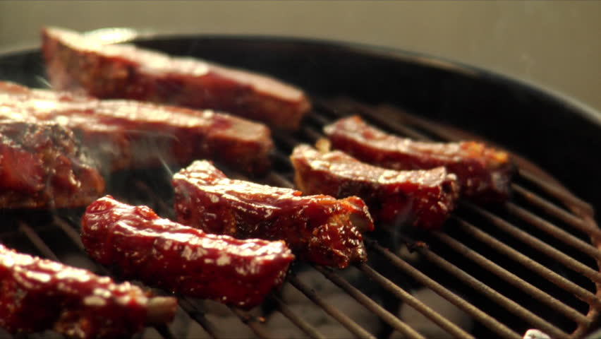 Brushing sauce on pork spareribs on the grill
