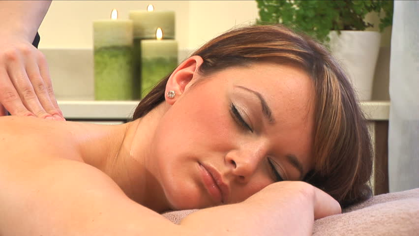 Beautiful brunette girl relaxes during massage at the health spa - HD stock footage clip