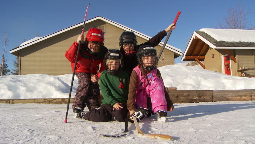 four young kids pose in hockey gear on backyard ice rink stock footage
