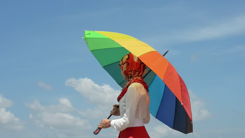 beautiful young muslimah women with colorful umbrella waving her hand isolated on blue sky background - HD stock footage clip