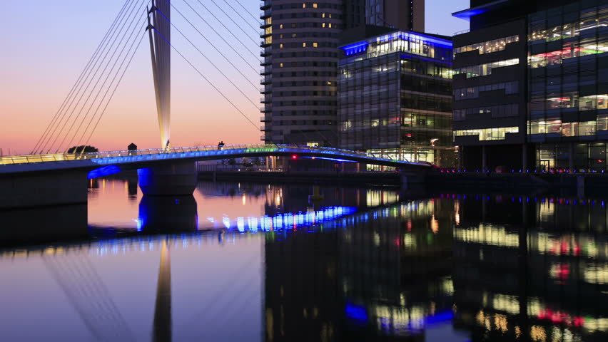 MANCHESTER, LANCASHIRE/ENGLAND - JUNE 2: Mediacity footbridge at dusk with changing colors floodlights on June 2, 2011 in Salford Quays. The swing bridge was built to serve MediaCity UK.