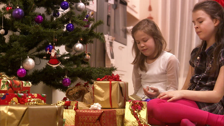Girls sitting by the Christmas tree