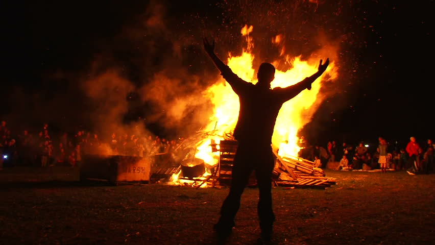 Man in front of large bonfire has both arms up high taking in the heat, filmed in slow motion.