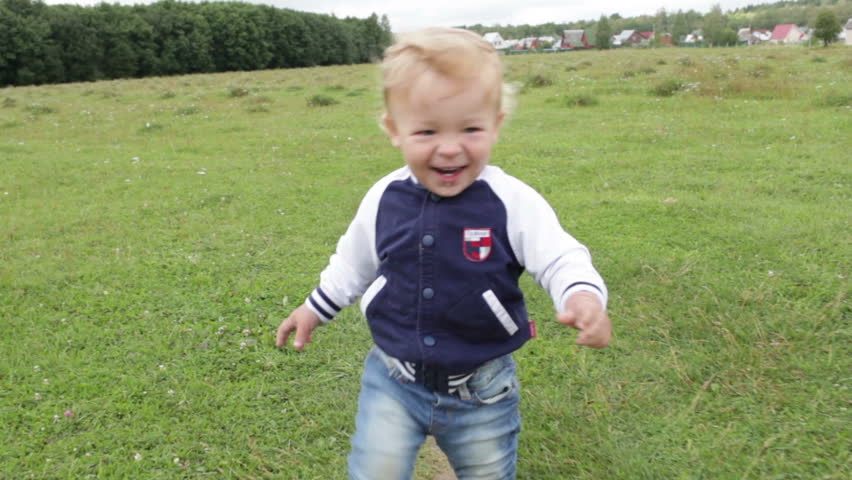 The one year old cute fair-head boy is making his first steps - HD stock video clip