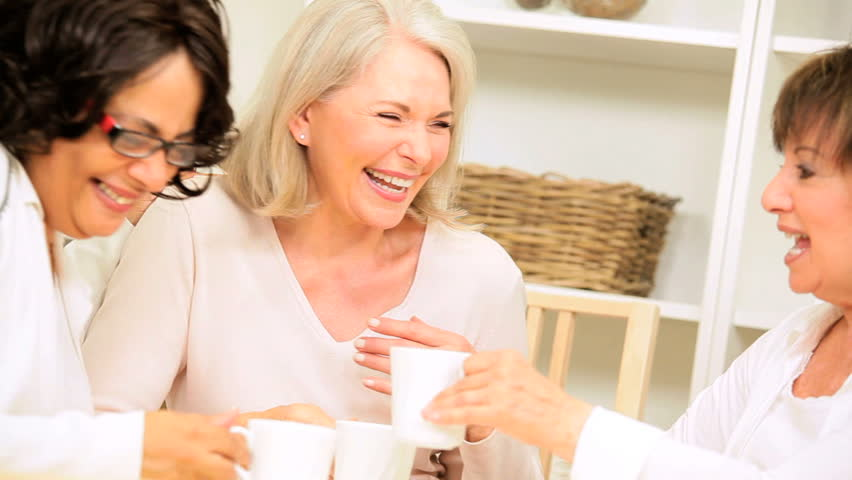 Multi ethnic older female friends enjoying coffee and gossip home - HD stock video clip