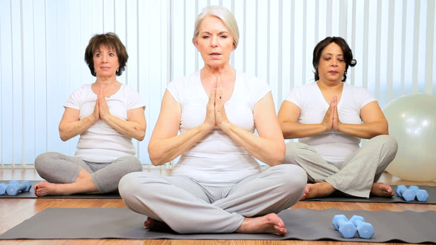 Older Caucasian female instructor teaching yoga to senior ladies - HD stock video clip