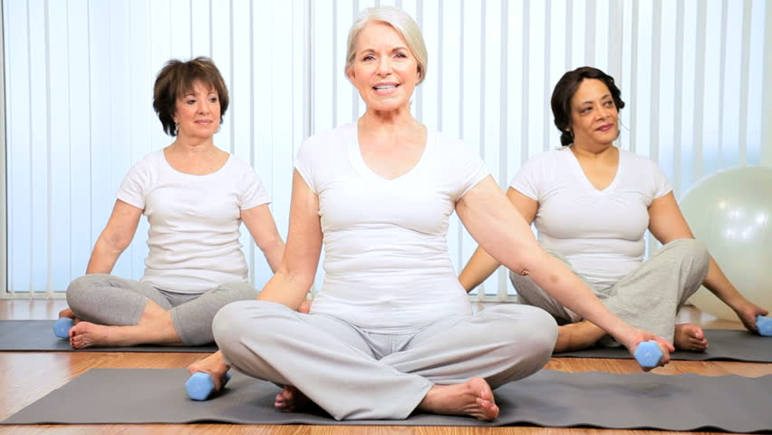 Older Caucasian female instructor teaching yoga to senior ladies - HD stock footage clip