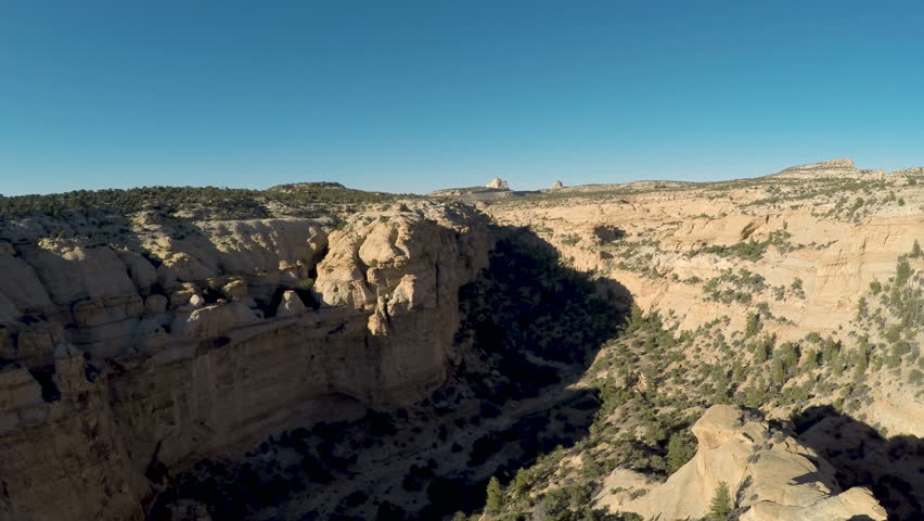 Aerial-Pull back from a view of a rugged desert vista and descending the cliff face of a massive monolith in the San Rafael Swell desert of Utah on a clear late afternoon day.