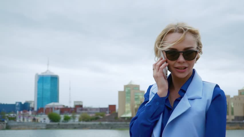 Young blond attractive woman walking in the park by the river and talking on the mobile phone. Blue shirt, business suit. | Shutterstock HD Video #26784493