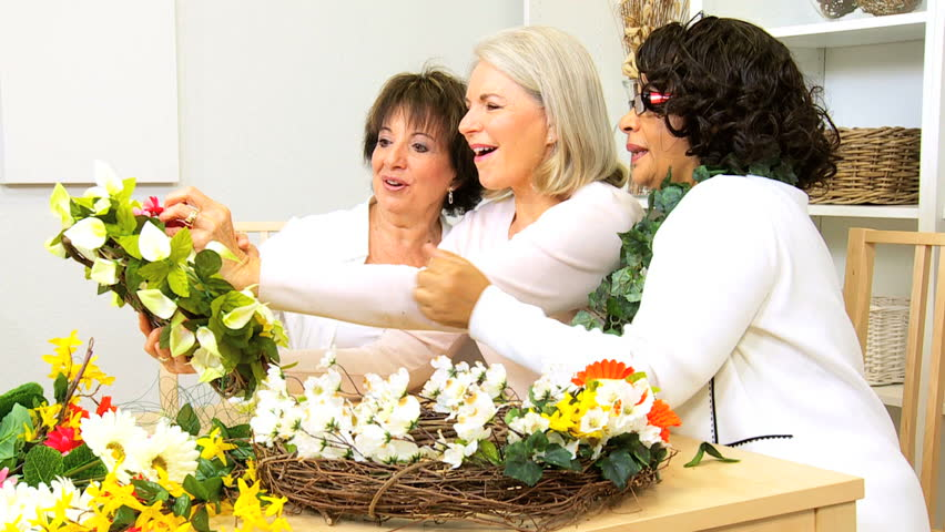 Senior ladies having fun leisure time together flower arranging