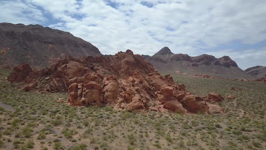 Aerial near Valley of Fire red rock desert landscape Nevada. Scenic desert landscape mountains. Natural ecological destination. Hot arid red multicolored rock formation wilderness. | Shutterstock HD Video #27076327