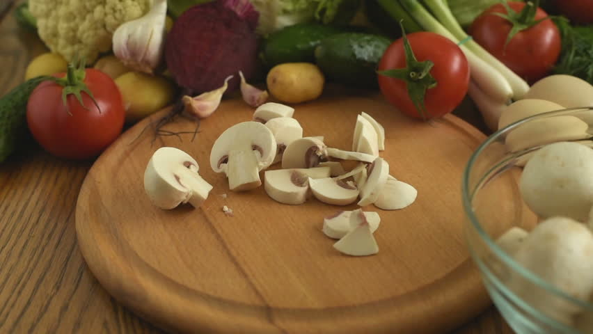 Cooking. Cutting fresh mushrooms. Cutting fresh vegetables. Chopping Vegetables Full HD1080p. Slicing mushrooms on a chopping board. chopping mushrooms on vegetables background. #27160450