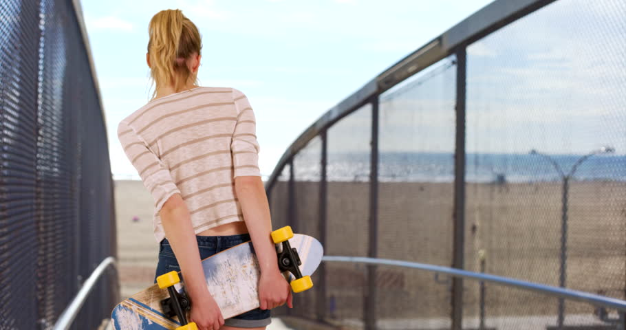 Young woman millennial skater with skateboard behind back rear view on walkway leading to California Beach. Skate board girl looking at ocean while waiting for friends to go to the boardwalk. 4k | Shutterstock HD Video #27185992