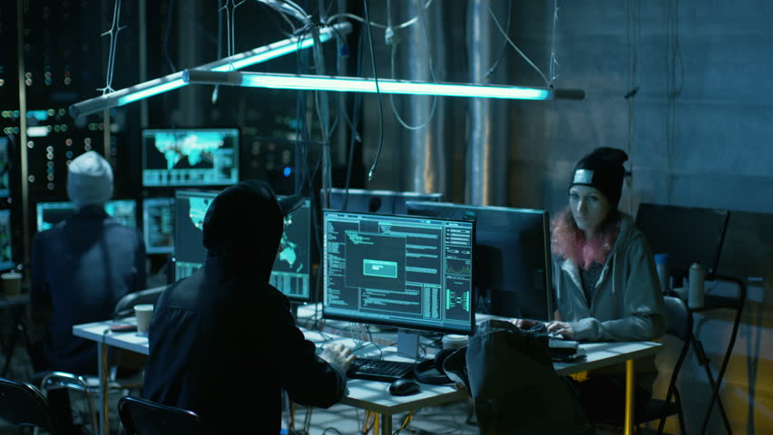 Team of Internationally Wanted Teenage Hackers Infect Servers and Infrastructure with Malware. Their Hideout is Dark, Neon Lit and Has Multiple Displays. Shot on RED EPIC-W 8K Helium Cinema Camera. | Shutterstock HD Video #27247462