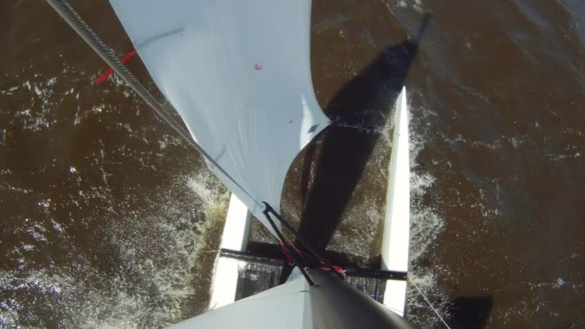 Catamaran cutting through the waves, sailing downwind over port, seen from the top of the mast