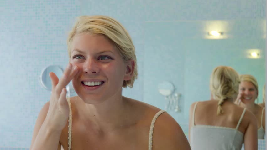 Female beauty, beautiful young caucasian woman applying cream on face in bathroom at home. Sequence - HD stock video clip