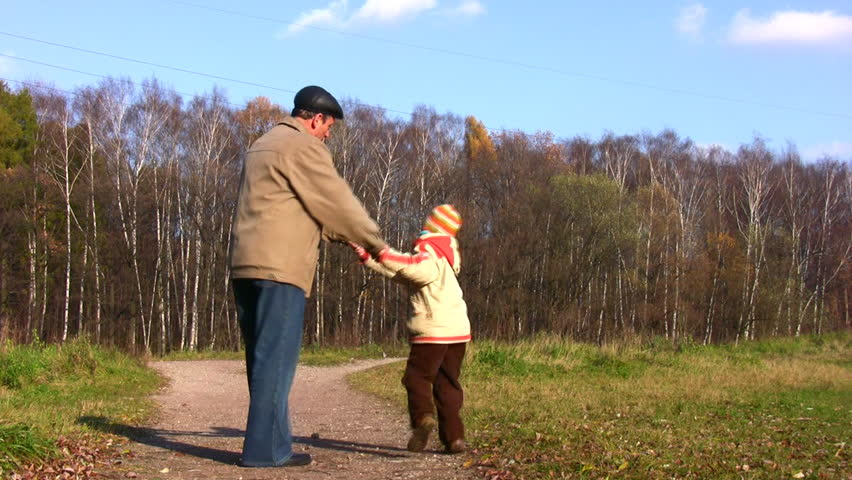 grandfather rotate boy in autumn park  - HD stock footage clip