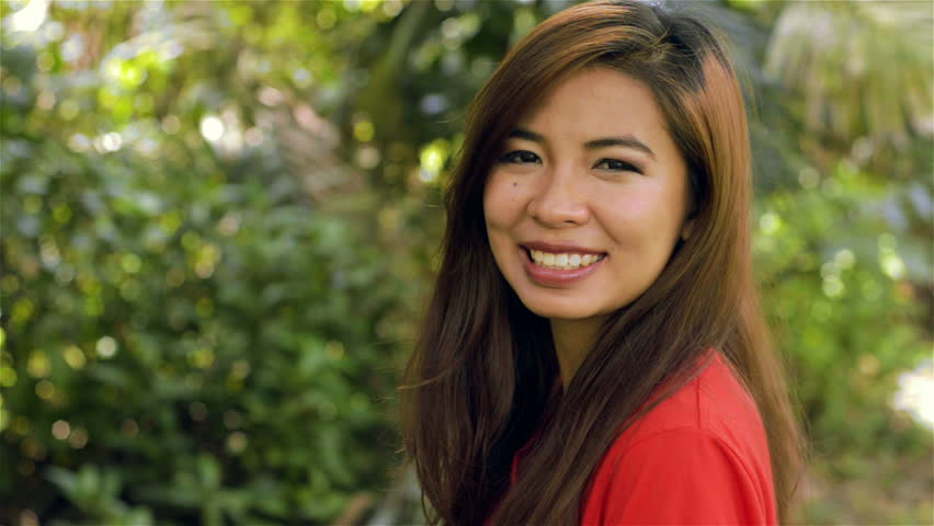 Young Asian woman turning to face the camera and smiling - dolly shot. - HD stock footage clip