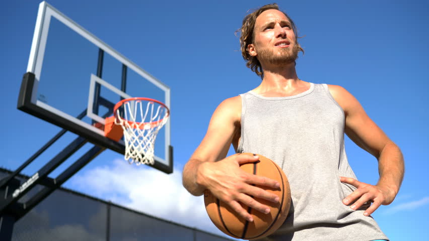 Basketball Player. Tired man holding basketball against blue sky. Young male is looking away on sunny day. He is standing at basketball court outside. #28027204
