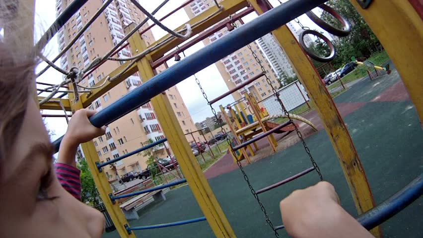 Girl rises on an iron ladder at playground in house yard