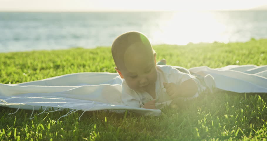 Young baby crawling for the first time on blanket on green grass by the ocean at sunset | Shutterstock HD Video #28179601
