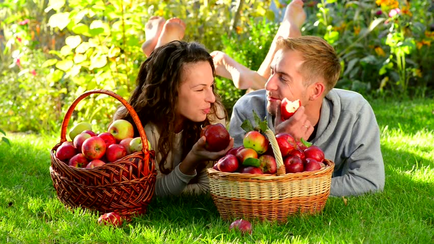 Happy Couple in Autumn Garden.Having Fun on the Grass and Eating Apples Healthy Food.Outdoor.Park.