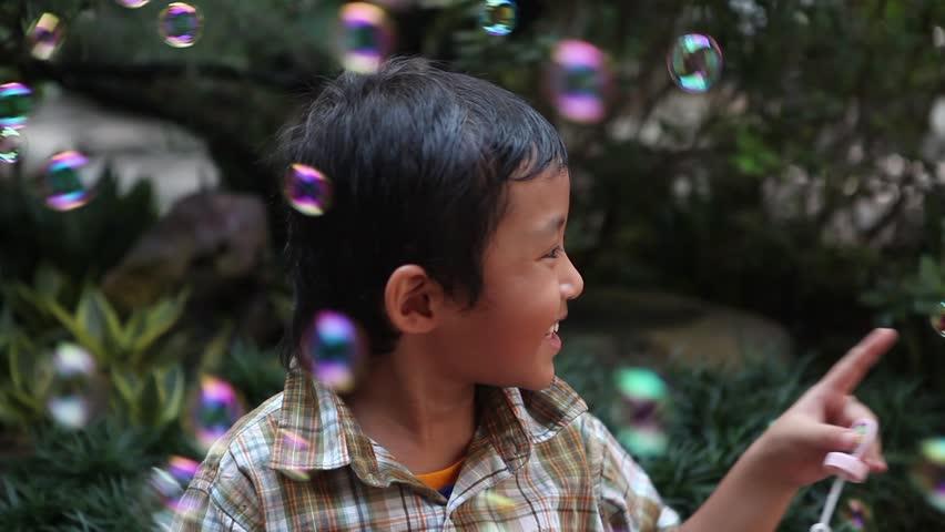 Cute little Asian boy having fun with bubbles