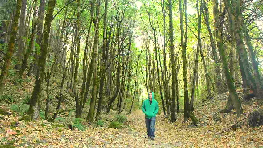 Man walks in dense forest on trail full of leaves in Oregon.