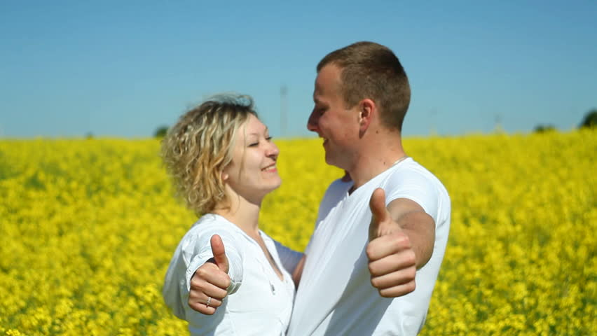 Sweet couple in a field of rape give thumbs up