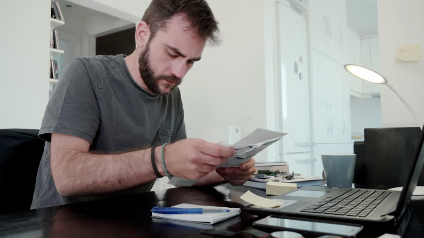 Young man overwhelmed by his bills at home.A young man at home calculates his living expenses and sums his bills and his overdue notices and falls into despair   Shutterstock HD Video #28294954