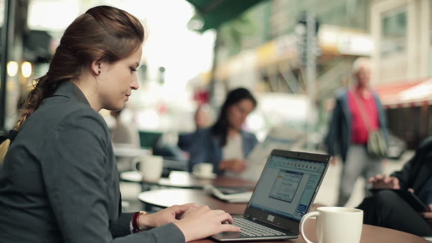 Young businesswoman working with laptop in the restaurant, outdoors