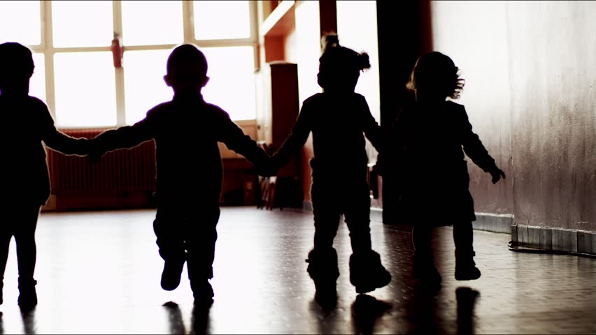 4 kids walk together in school in slow motion. silhouettes.