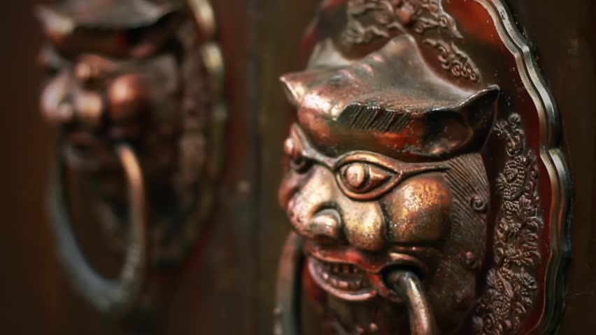 "CHENGDU, CHINA - SEPTEMBER 10: Lions knocker of old door in the ""Kuan Alley & Zhai Alley"" historical culture protectorate on September 10, 2012 in Chengdu, China."