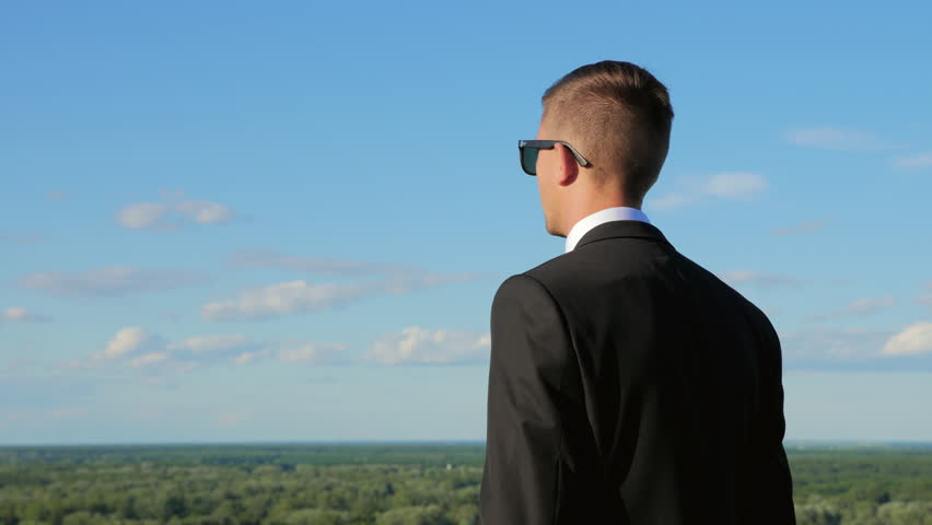 A young man in a suit looks into the distance standing on a hill against the blue sky at sunset. Middle shot #28588903