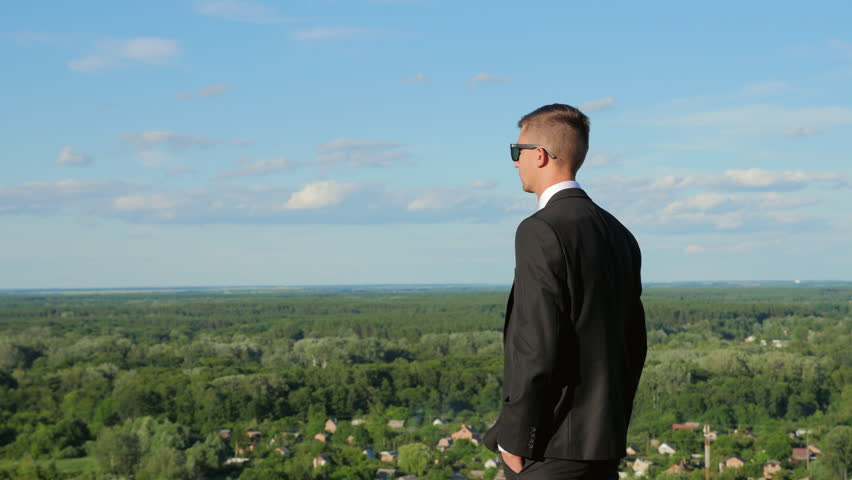 A young man in a suit looks into the distance standing on a hill against the blue sky at sunset. #28588912
