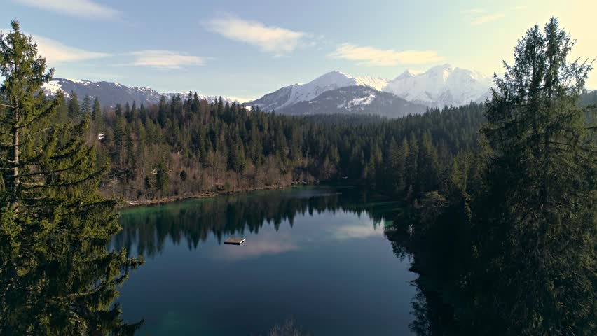 Aerial footage of a beautiful lake in the forest with mountains in the background. Shot in Flims, Switzerland in 4k quality. | Shutterstock HD Video #28631446
