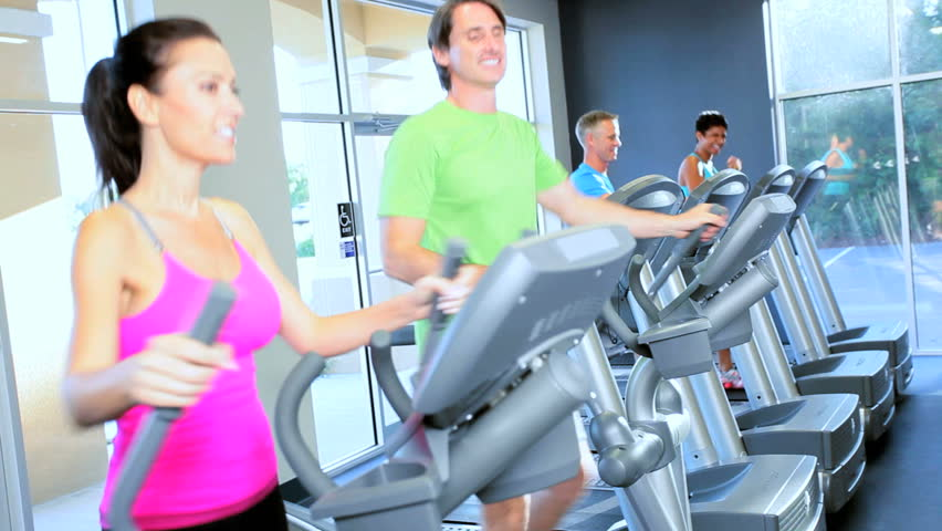 Multi ethnic gym members exercising on modern cross walkers and treadmills as part of healthy lifestyle - HD stock video clip