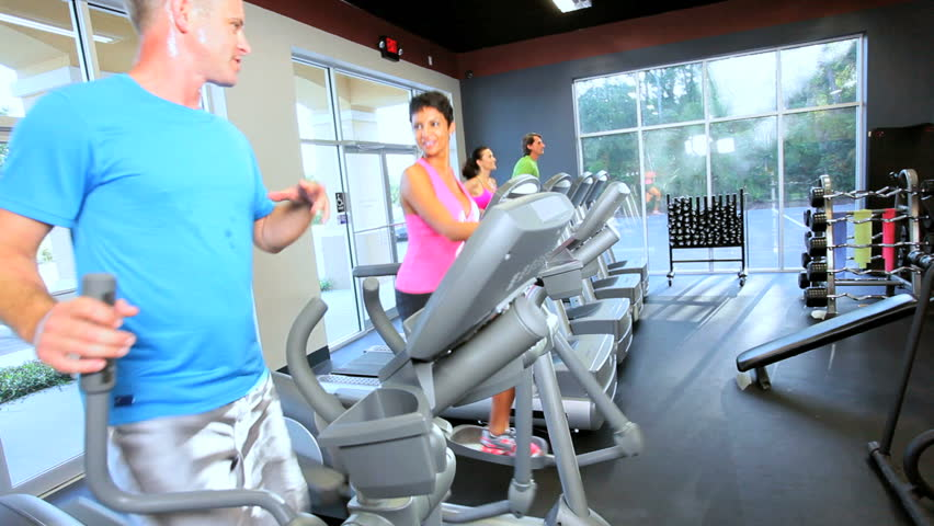 Multi ethnic gym members exercising on modern cross trainers and treadmills as part of healthy lifestyle - HD stock footage clip