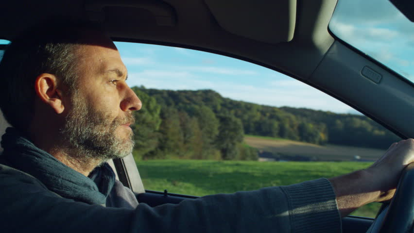 a mature man inside his car, driving on a summer day - HD stock video clip
