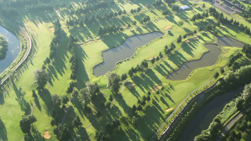 Low-altitude airplane view of bright green fairways and country club at dawn #2881213
