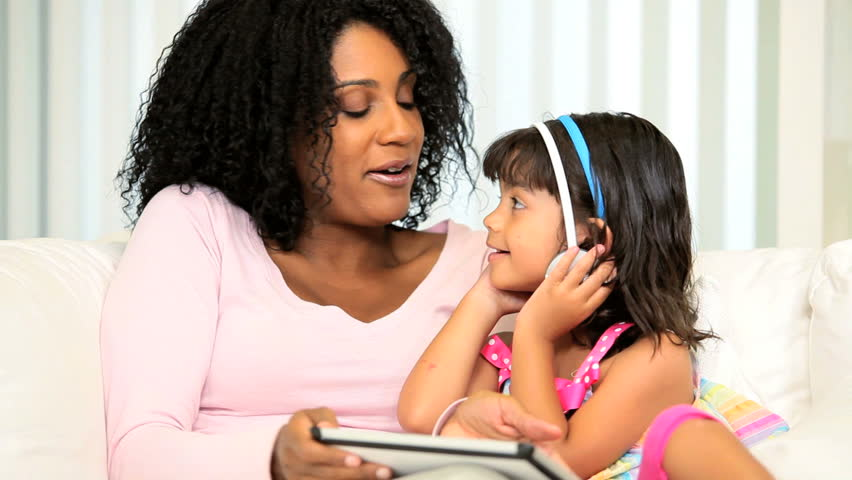 Cute little ethnic girl sitting with young mom wearing earphones using tablet - HD stock video clip