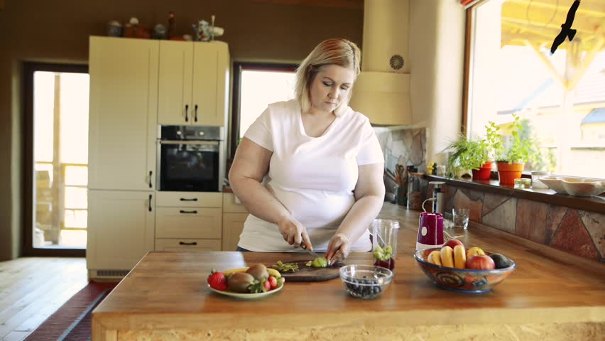 Attractive overweight woman preparing healthy smoothie. #28895794
