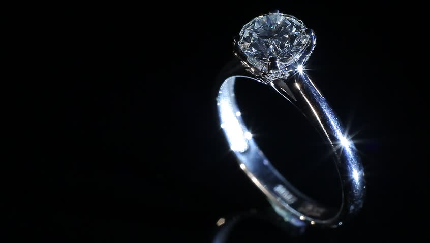 Silver beautiful ring with brilliant turning on themselves against a black background  - HD stock video clip