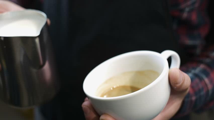 Barista draws milk over a coffee - making latte art for cappuccino | Shutterstock HD Video #28930480