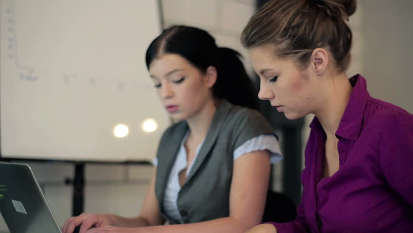 Two young businesswomen with laptop and documents in the office  - HD stock footage clip