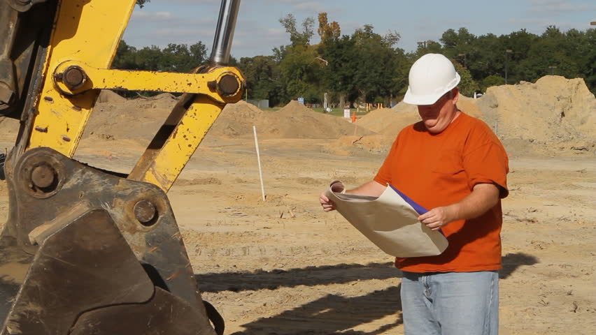 Construction foreman stands by heavy machinery at an excavation site and sends a text message after reading some blueprints. - HD stock footage clip
